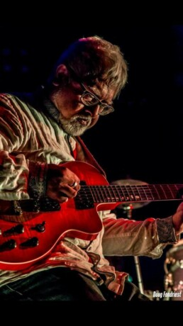 Fareed Haque playing a red electric guitar.