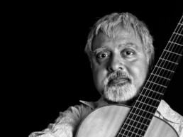 Image of Fareed Haque holding an acoustic guitar.